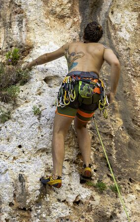 Salento - Italy: June 4, 2017: young athlete climbs on a rocky rock in the Salento countryside