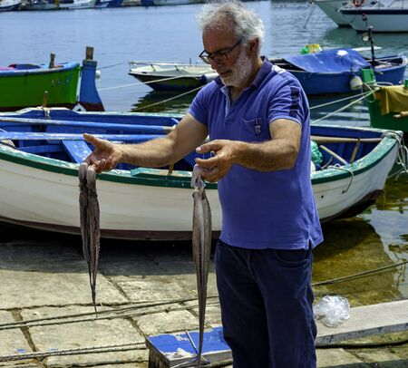 Bisceglie - Italy. June 2, 2017: Fisherman caught an octopus in the sea and beats him on the asphalt to make it softer. In this way the octopus tentacles will bake and the meat becomes softer Editorial