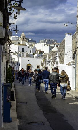 Alberobello, Italy - April 17, 2017: Tourists visit Alberobello, a small town and comune of the Metropolitan City of Bari. It has about 10,700 inhabitants and is famous for its unique trullo buildings.