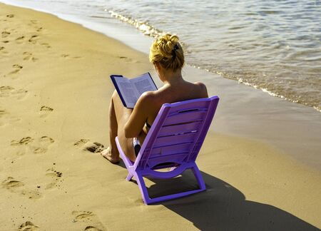 Young woman reading a book at the beach Editorial