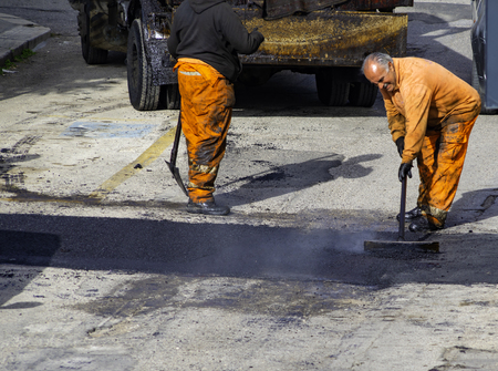 Worker regulate laying new asphalt to patch a bump in the road. Banque d'images