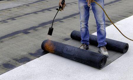 Roofer che installa rotoli di membrana impermeabilizzante bituminosa per l'impermeabilizzazione di un terrazzo Archivio Fotografico
