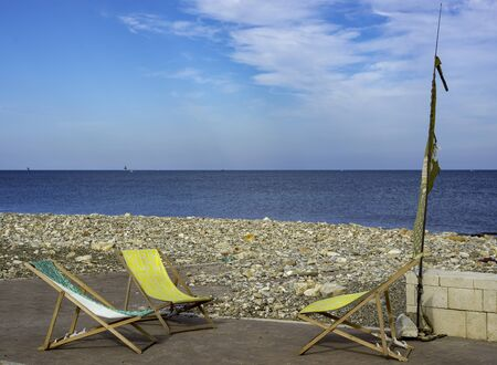 deckchairs abandoned beside a pebble beach on a cloudy day Standard-Bild