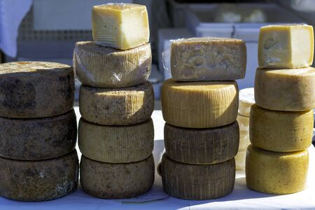 forms of pecorino cheese arranged for sale in an agricultural market in southern Italy
