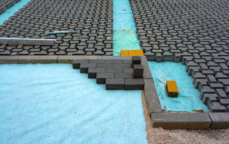 Heap of interlocking paving stones; Material for paving works on sheet of nonwoven