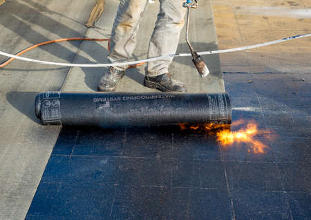 """Worker preparing part of bitumen roofing felt roll for melting by gas heater torch flame. On the back of the sheath there is the stamp """"Made in Italy"""" product."""