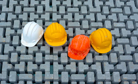 Safety helmets for construction workers resting on the pavement with interlocking blocks during work break