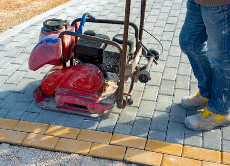 Vibrator with rubber plate for compacting paving with interlocking blocks