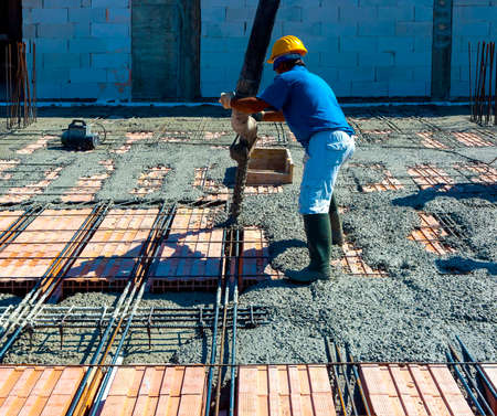 Construction worker compacting liquid cement in reinforcement form work during concreting floors pouring works Standard-Bild