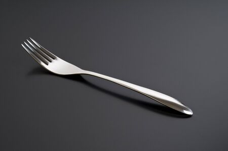 silver fork on black table photo