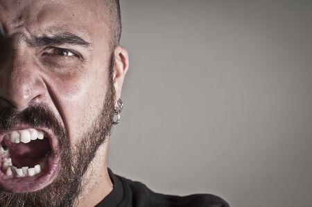 mid-frontal portrait of a man yelling on grey background Stock Photo