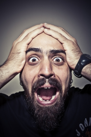 terrified man on grey background photo