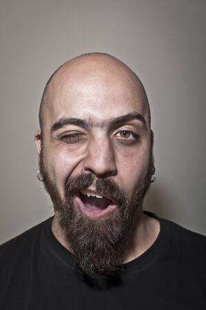 a beard: Man with beard winks on grey background Stock Photo