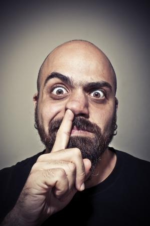 hombre con barba: hombre con su dedo en la nariz sobre fondo oscuro