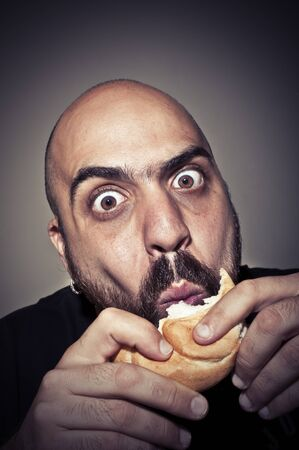 nice food: funny man eating a sandwich on dark background