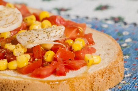bruschetta with tomato, onion and corn on blue tablecloth on the table photo