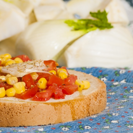 bruschetta with tomato, onion and corn on blue tablecloth with fennel and Brussels sprouts Stock Photo - 12954687