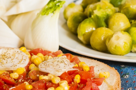 bruschetta with tomato, onion and corn on blue tablecloth with fennel and Brussels sprouts photo