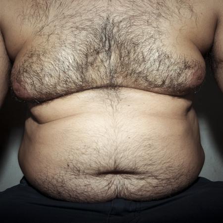 pancia grassa: pancia uomo grasso e peloso con le mani