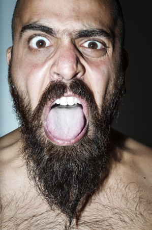 Man with beard with frightening expressions of anger photo