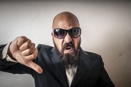 man bouncer with sunglasses and negative expression on white background photo