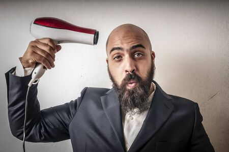 man bearded and jacket with hairdraier and funny expressions on white background Stock Photo - 15355989