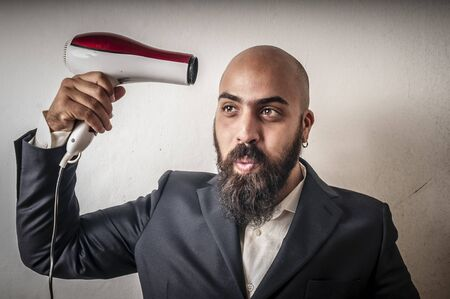 man bearded and jacket with hairdraier and funny expressions on white background Stock Photo - 15356022