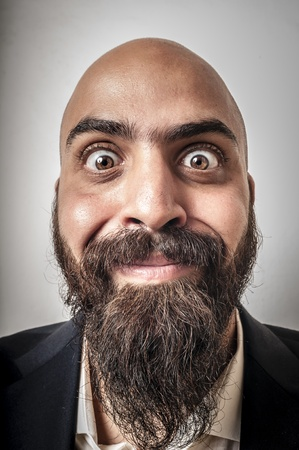 gente loca: hombre con barba y chaqueta elegante y expresiones divertidas en el fondo blanco Foto de archivo