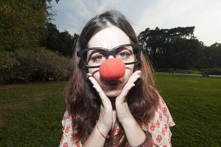 nariz roja: chica triste payaso con nariz roja en el parque en Mil�n Foto de archivo