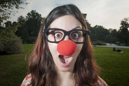 nariz roja: Chica de payaso sorprendido con la nariz roja en el parque en milan Foto de archivo