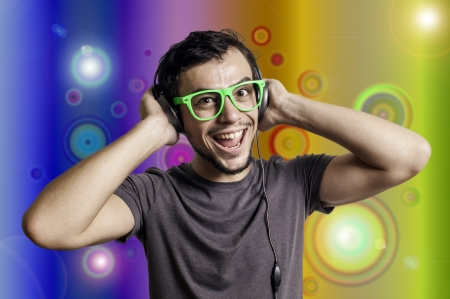 Crazy guy with headphones and green glasses on colorful background photo