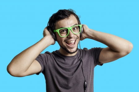 Crazy guy with headphones on blue background Stock Photo - 15483224