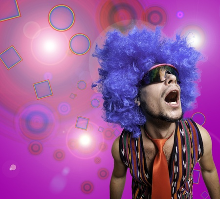 crazy guy with sunglasses and blue wig on colorful background photo