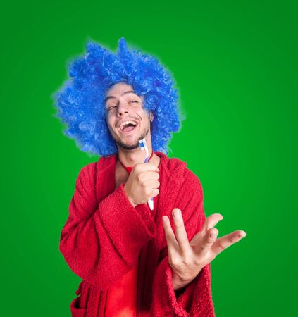 red bathrobe: crazy guy with a toothbrush, wig and bathrobe singing on green background Stock Photo