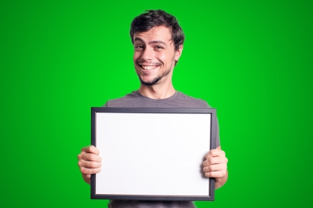 smiling guy holding empty board on green background photo