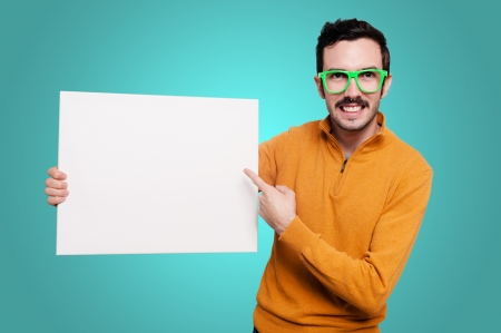 man with orange sweater and green glasses holding blank white board on blue background Stock Photo
