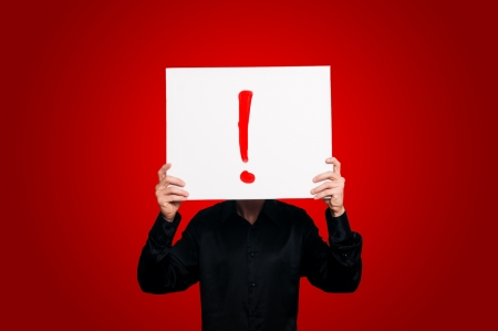 exclamation mark: man holding sign exclamation mark on red backgound