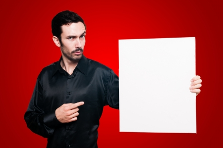 man with mustache and black jacket holding blank white board on red background Stock Photo - 15720813