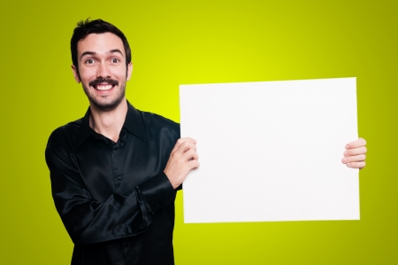 smiling man with mustache and black jacket holding blank white board on yellow background photo