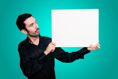 man with mustache and black jacket holding blank white board on blue background photo