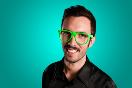smiling man with green eyeglasses and black jacket on blue background photo