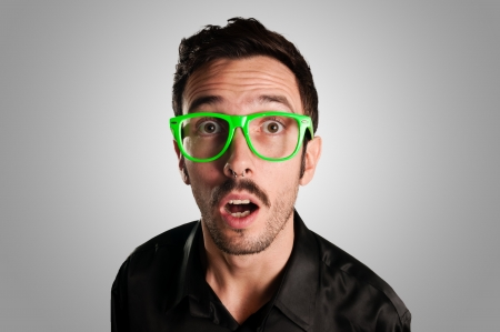 astonished man with green eyeglasses on gray background photo