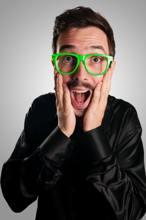 frightened man with green eyeglasses and blackjacket on gray background photo