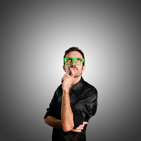 thoughtful man with green eyeglasses and gray background Stock Photo - 15784727