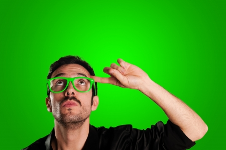 thoughtful man with green eyeglasses and green background Stockfoto