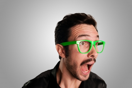 man schreeuwen met groene bril op grijze achtergrond Stockfoto