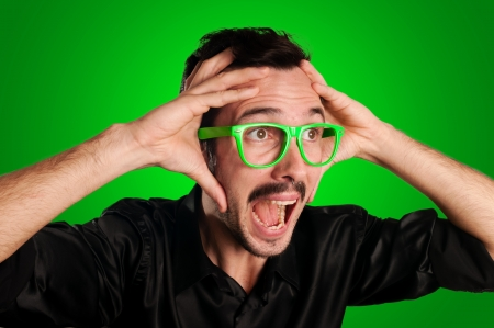 man screaming with green eyeglasses on green background photo