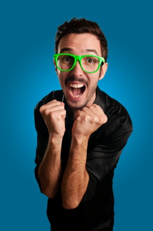 man screaming with green eyeglasses on blue  background