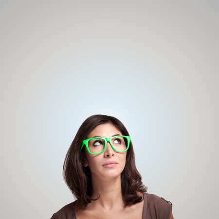 beautiful girl thinking with green eyeglasses on gray background Stock Photo - 15784730