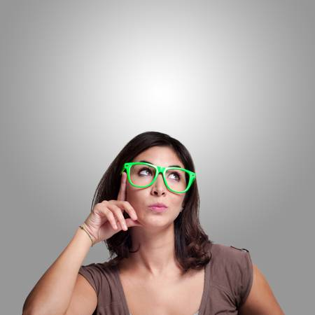 beautiful girl thinking with green eyeglasses on gray background photo
